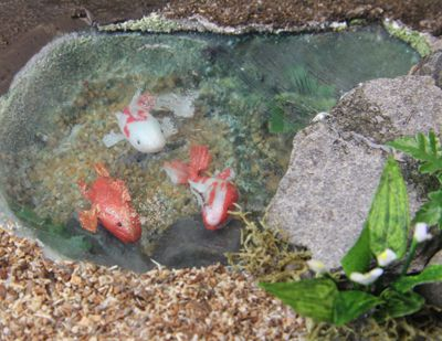 Dollhouse koi pond with still and moving water surfaces created on clear styrene sheet.