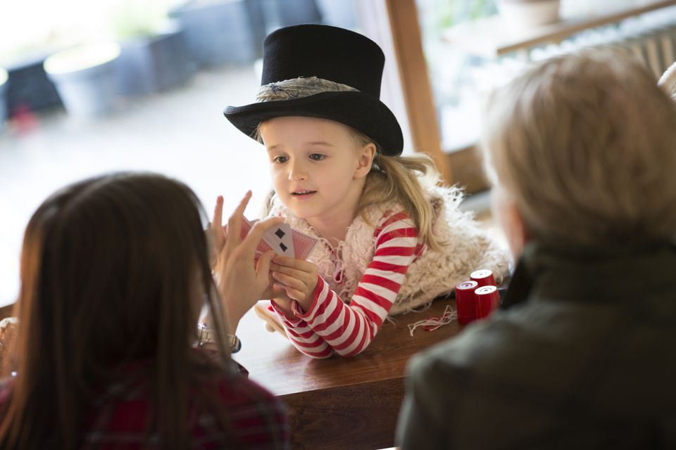 Girl (4-5) in top hat, performing magic trick for family