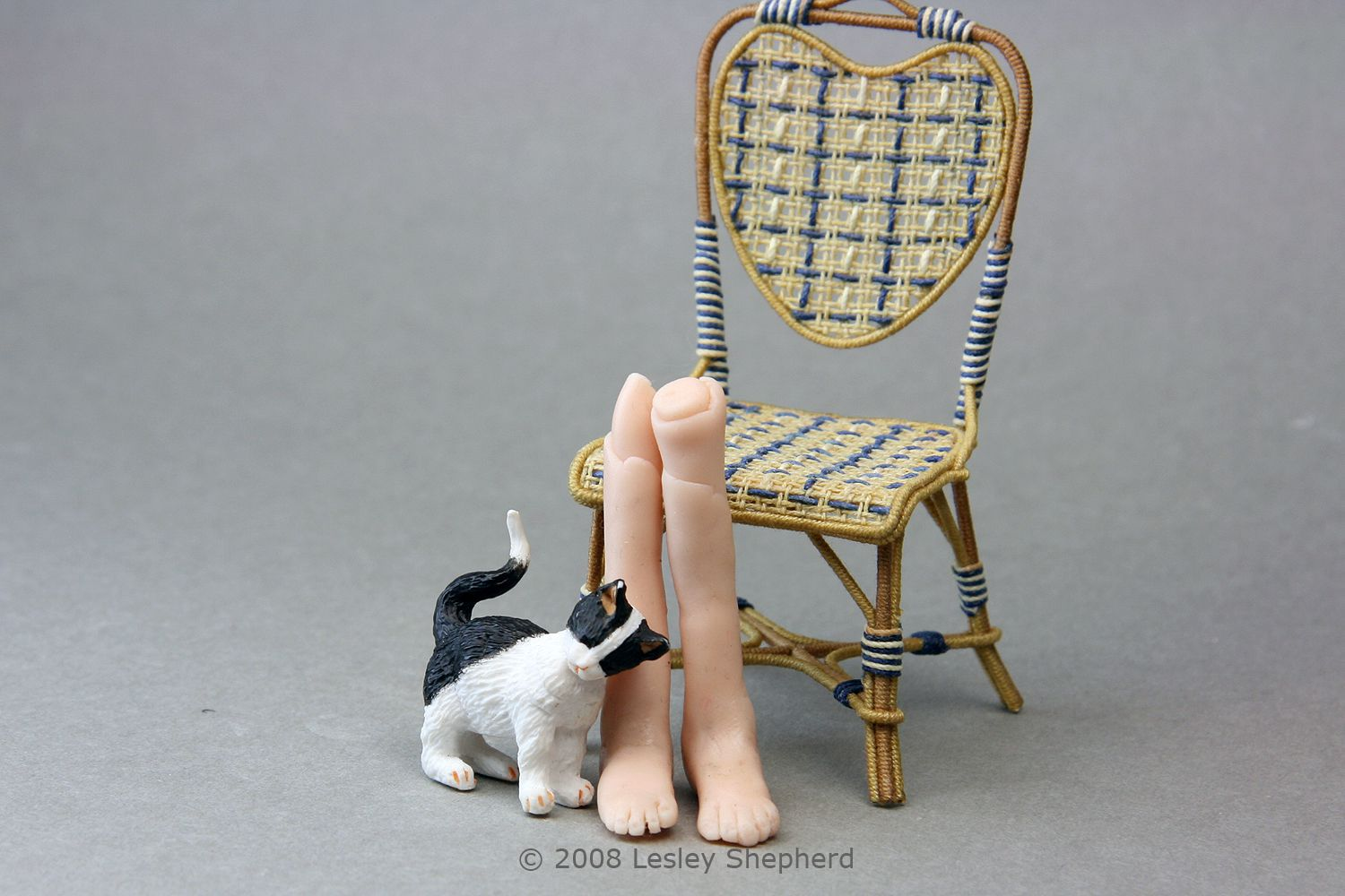 A pair of bare doll feet made from polymer clay for a 1:12 scale doll next to a miniature cat