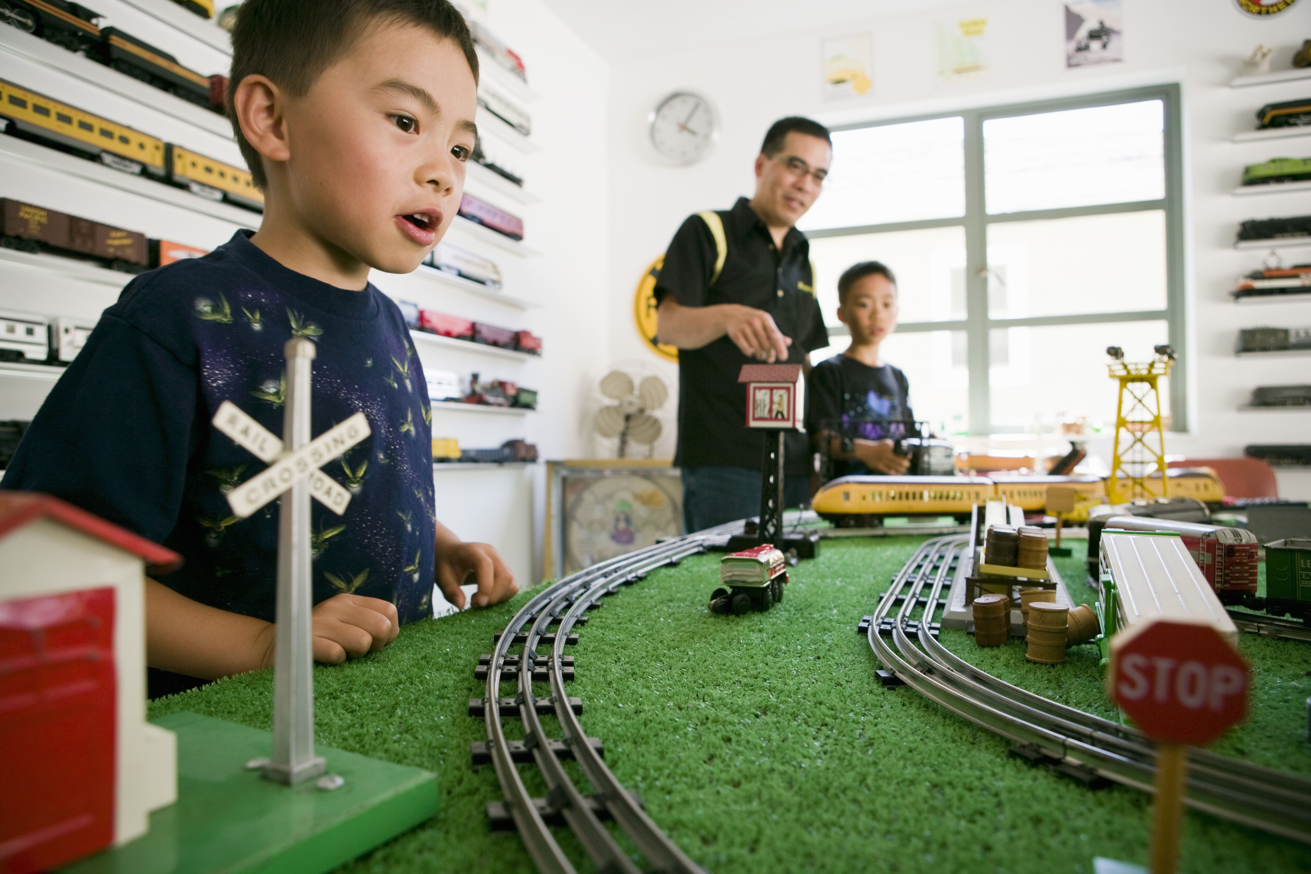 Father and sons playing with train set