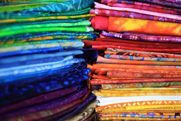 Piles of folded batik fabric in a multitude of colors.