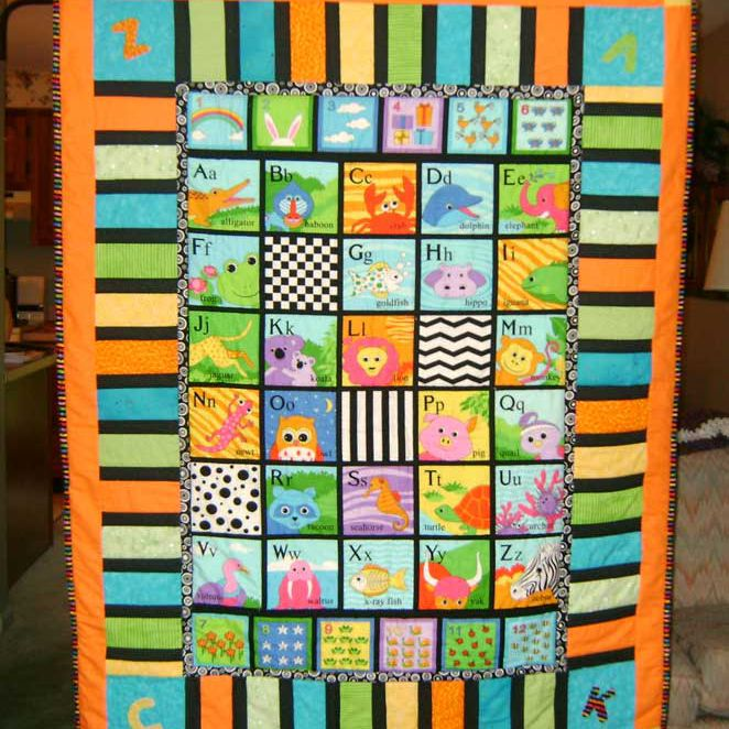 Orange baby quilt with animals for each letter of the alphabet.