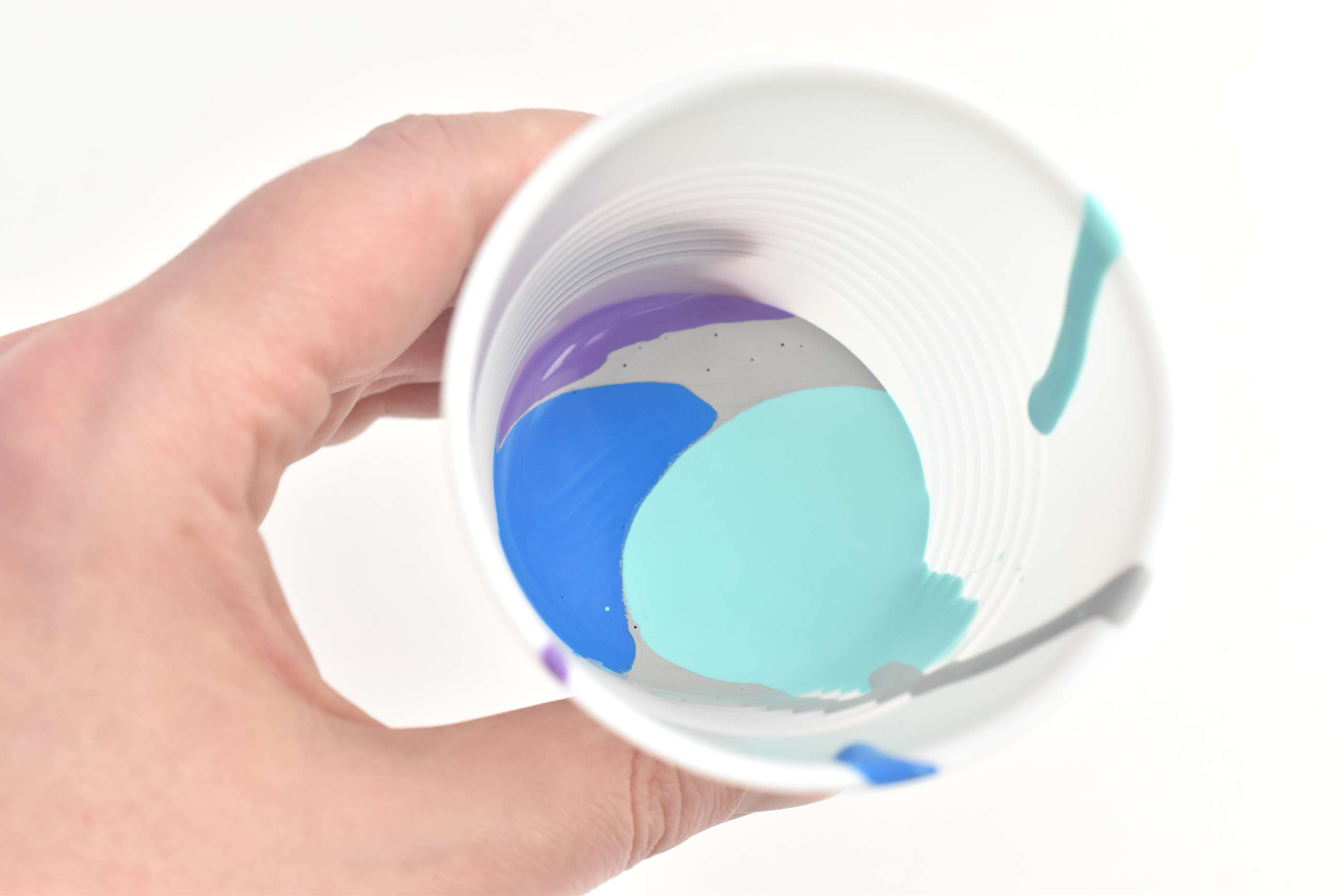 A hand holding a cup of aqua, blue, gray, and purple paint for pouring