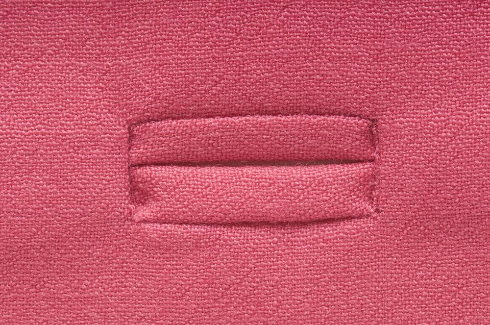Buttonhole sewn into pink fabric, close-up