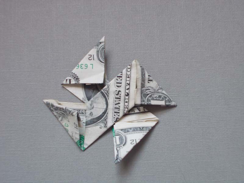 A dollar bill in stage five of an origami star