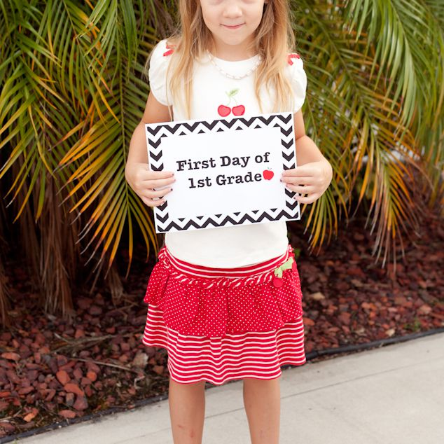A girl holding a first day of 1st grade sign.