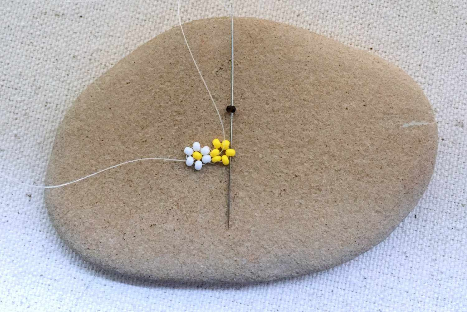 Adding the second flower of a daisy chain beadwork