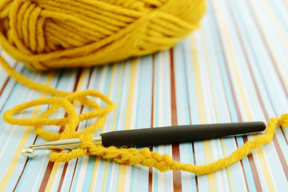 Ball Of Wool With Crochet Hook On Striped Paper