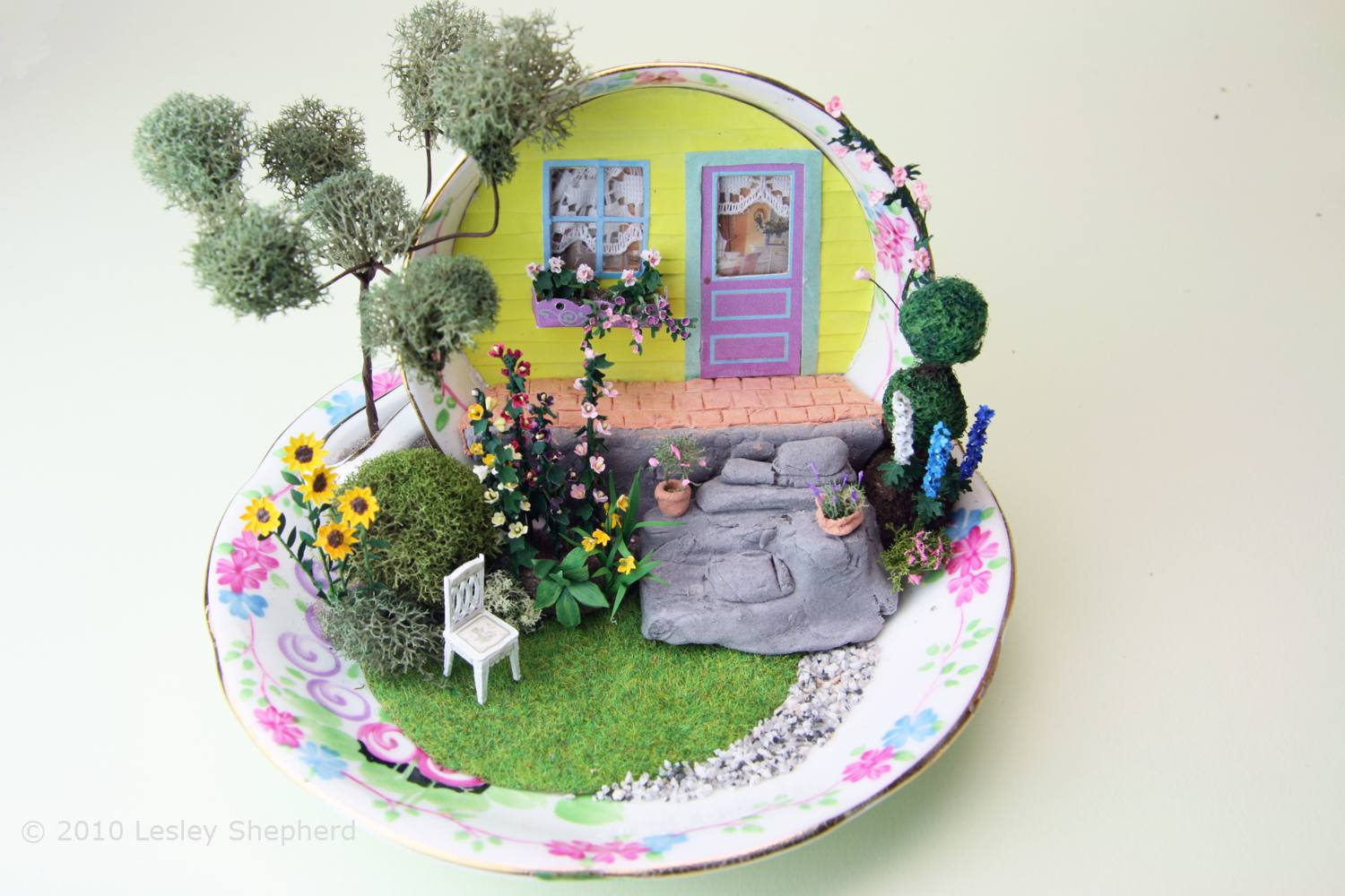 A 1:48 scale landscaped garden and cottage built in a tea cup.