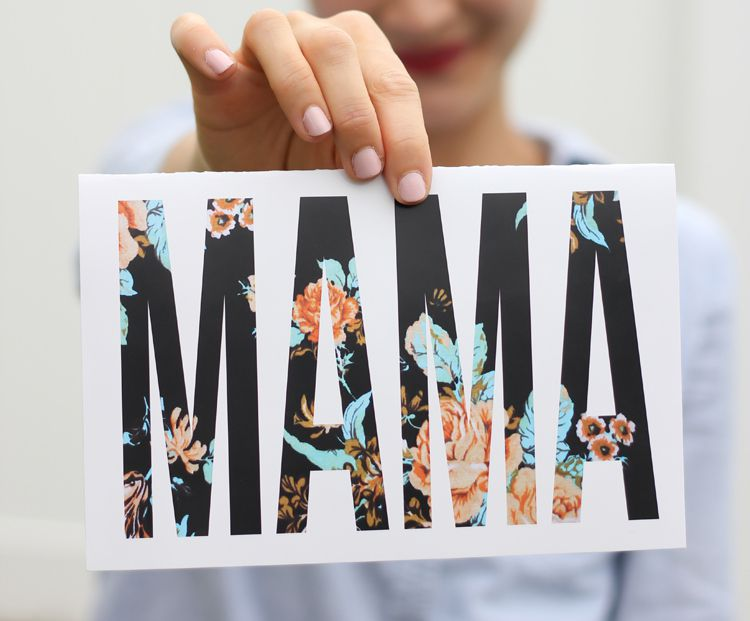 """A woman holding a card that says """"Mama"""""""