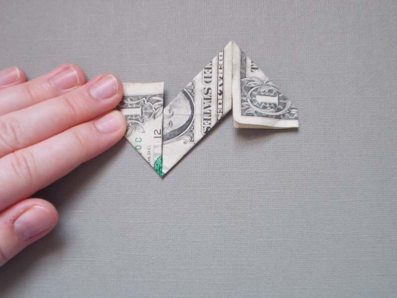 A dollar bill in stage three of an origami star