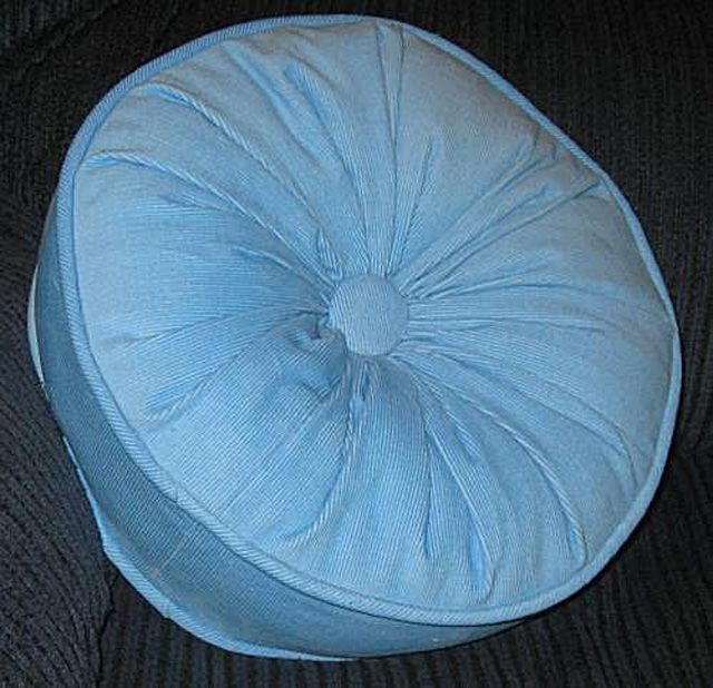 Round pillow with straight sides, a gathered center and a covered button in the Center of the Front and back of the pillow
