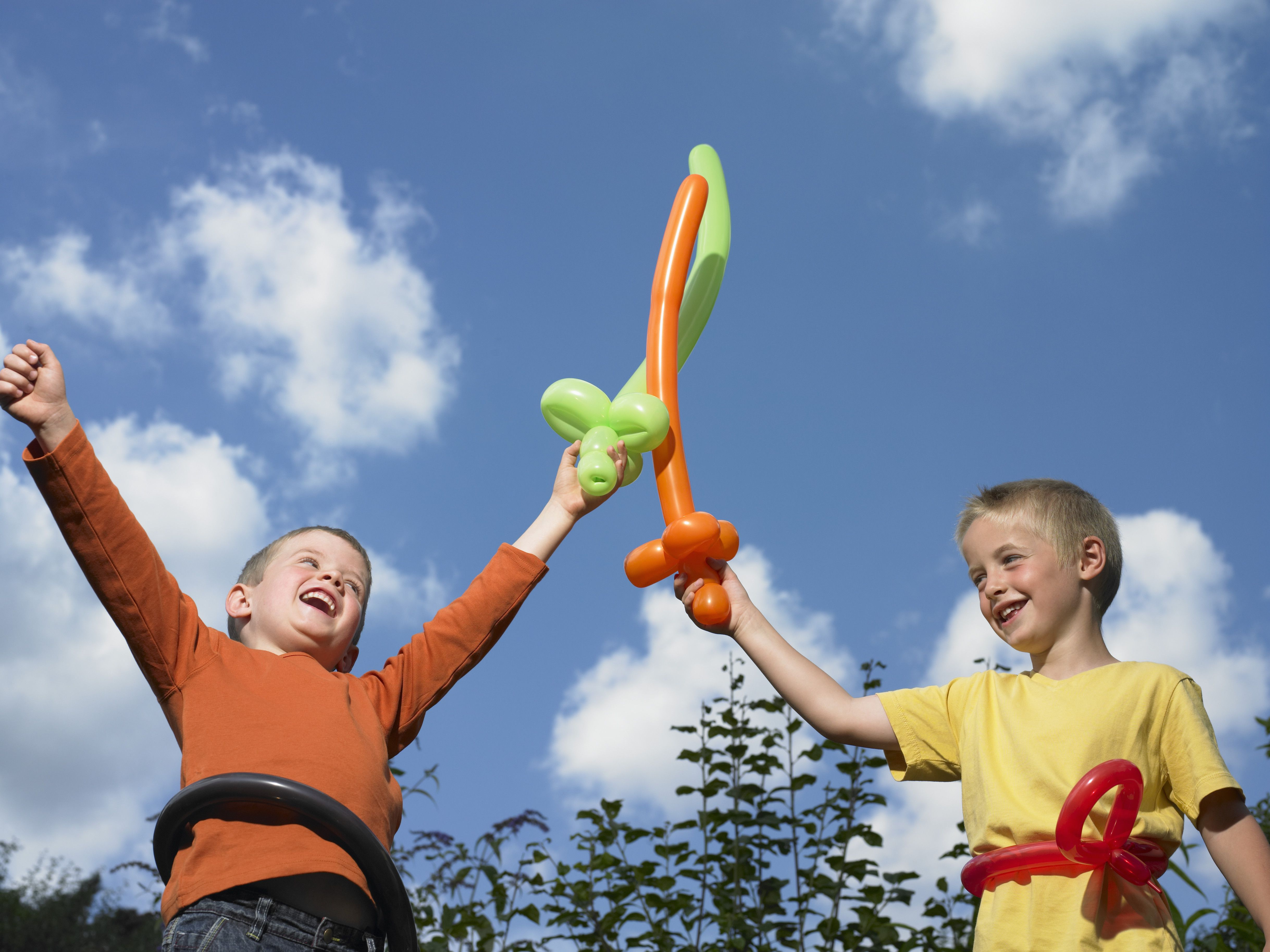 Two boys (5-7) playing with balloon swords, laughing, low angle view