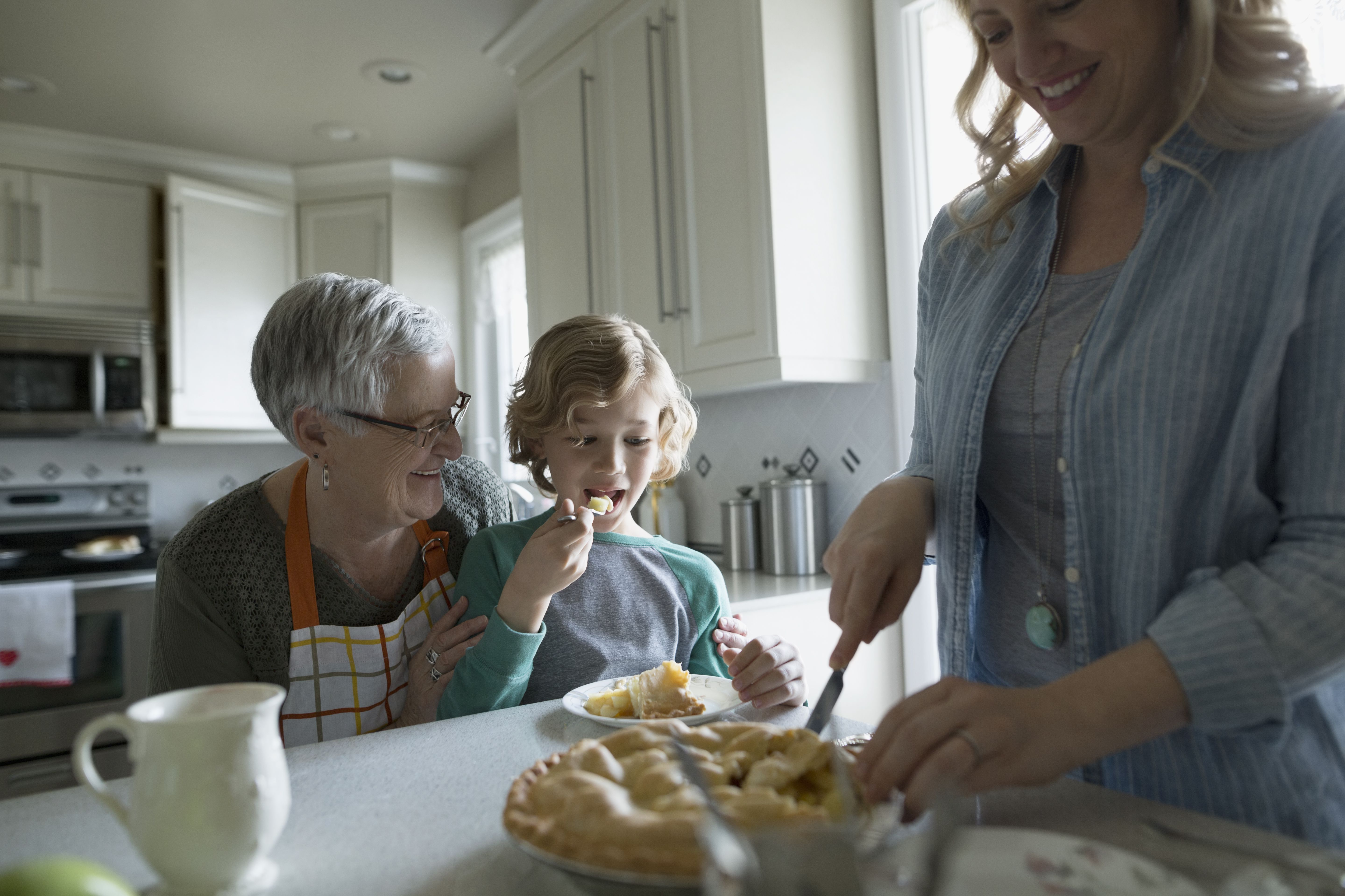 Multi-generation family eating homemade pie in kitchen