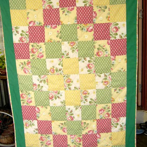 Green baby quilt with different-colored squares.