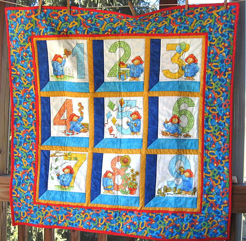 Paddington baby quilt hanging from a clothespin line.