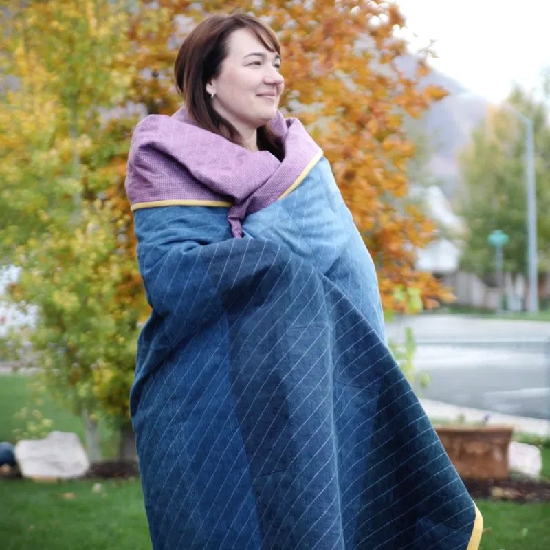 A woman wrapped up in a denim quilt
