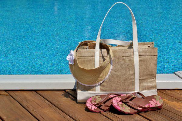 Beach bag with flip flops and a sun visor sitting on a pool deck