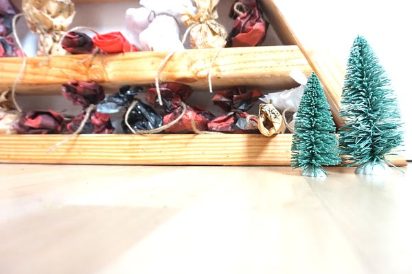 A close up of a DIY wood advent calendar with mini bottle brush trees in front of it.