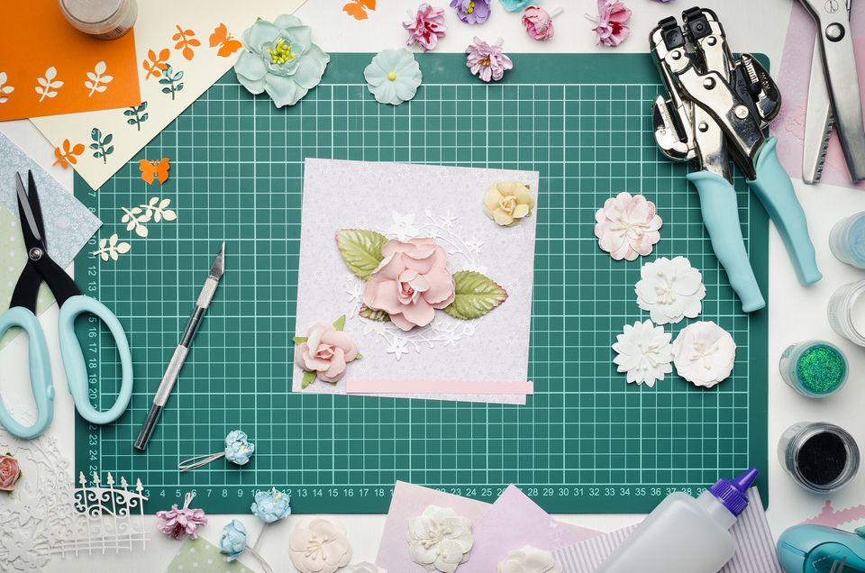 Multi-colored paper crafts on the cutting mat and scrapbooking tools