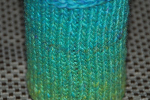 Knit cozy for a bottle or can.