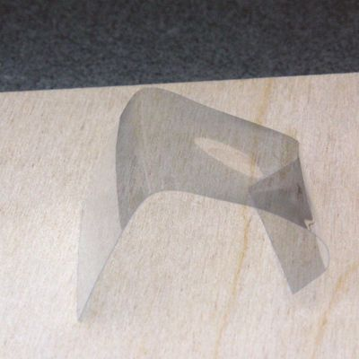 Paper thin sheet acrylic bent in a simple jig using an embossing heat tool.