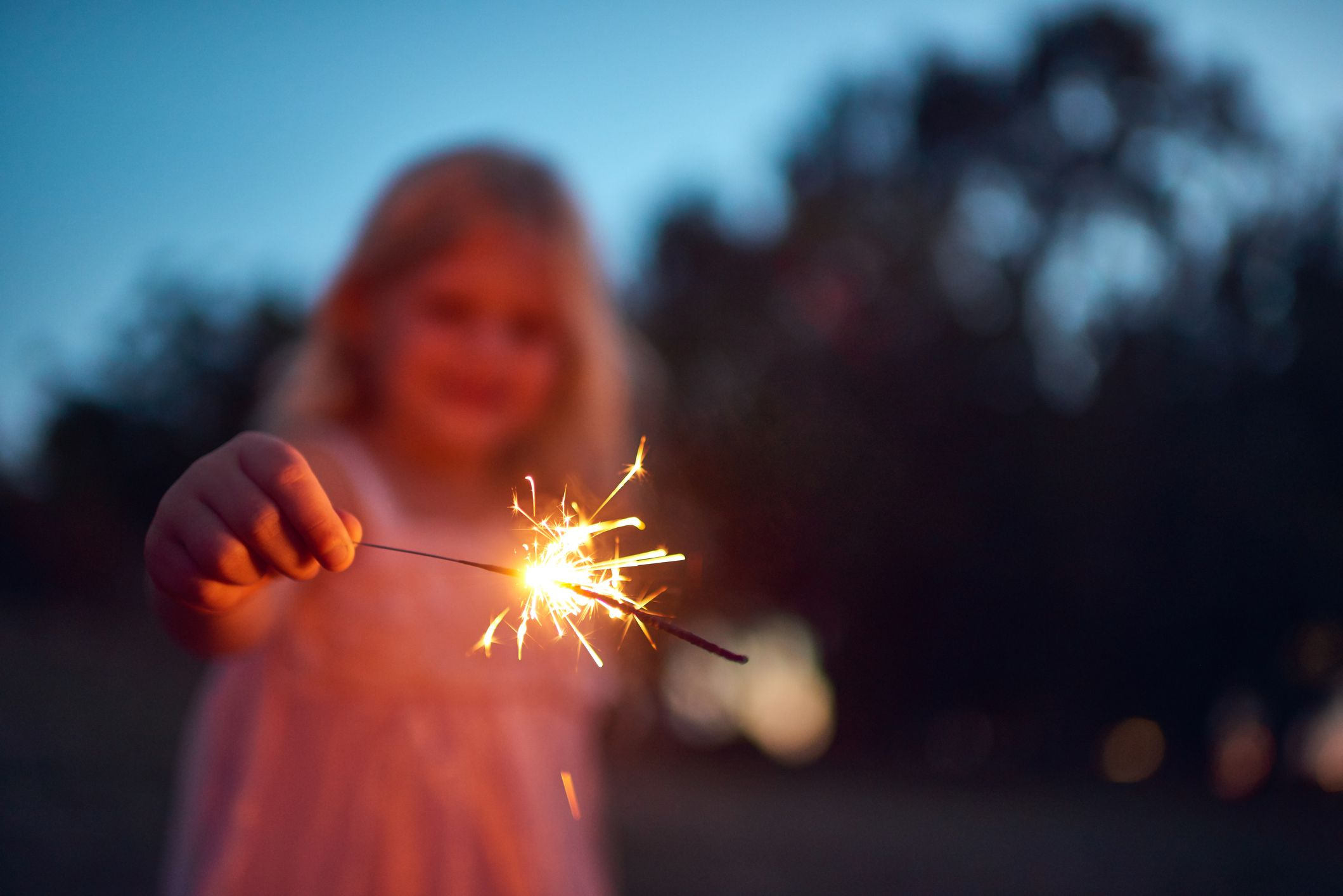 A girl playing with a sprakler firework