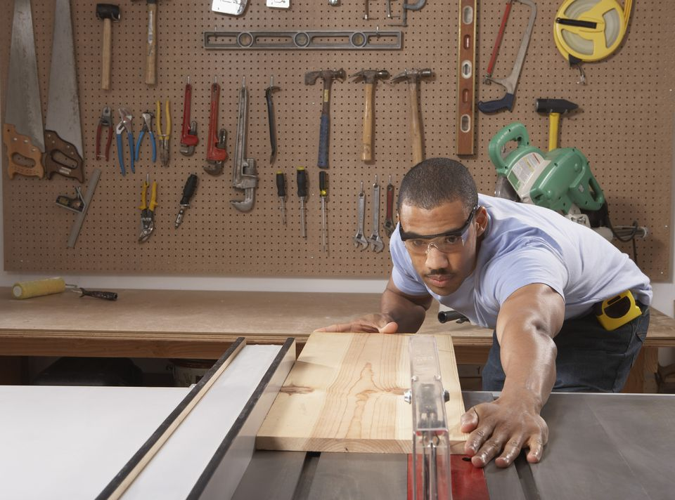Carpenter Cutting Wooden Plank in a Workshop