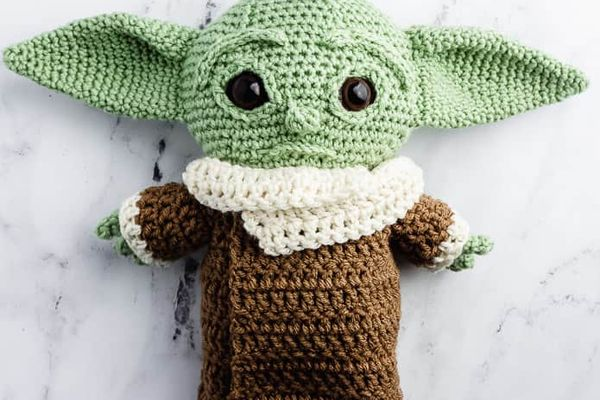 A crocheted baby Yoda laying on a table