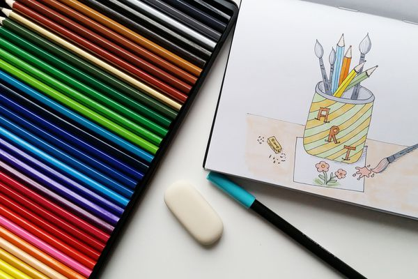 High Angle View Of Drawing On Paper With Multi Colored Pencils At Table