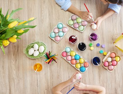 Overhead view of woman and daughters hands painting easter eggs at table