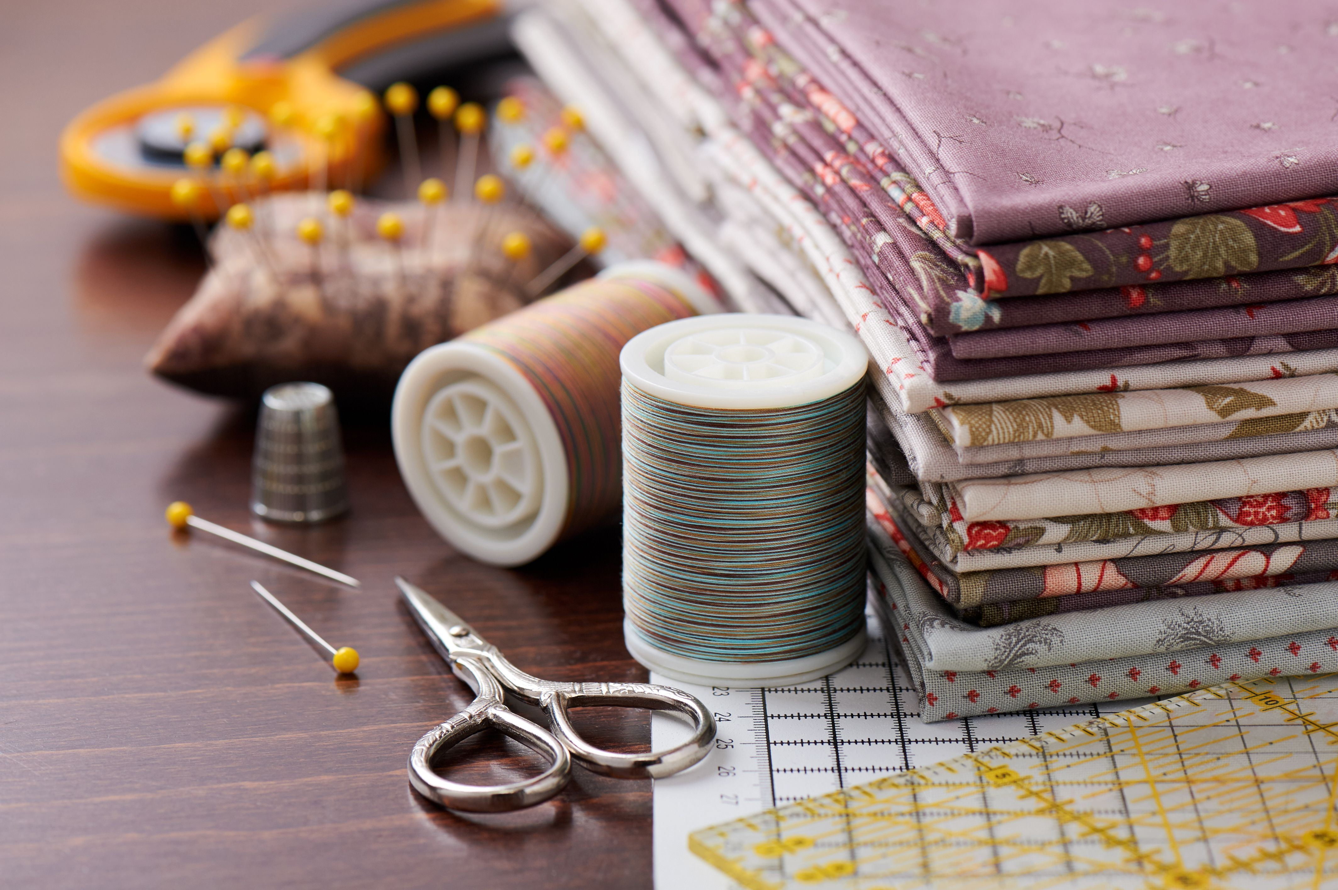 Stack of fabric for patchwork on craft mat, sewing accessories on wooden surface