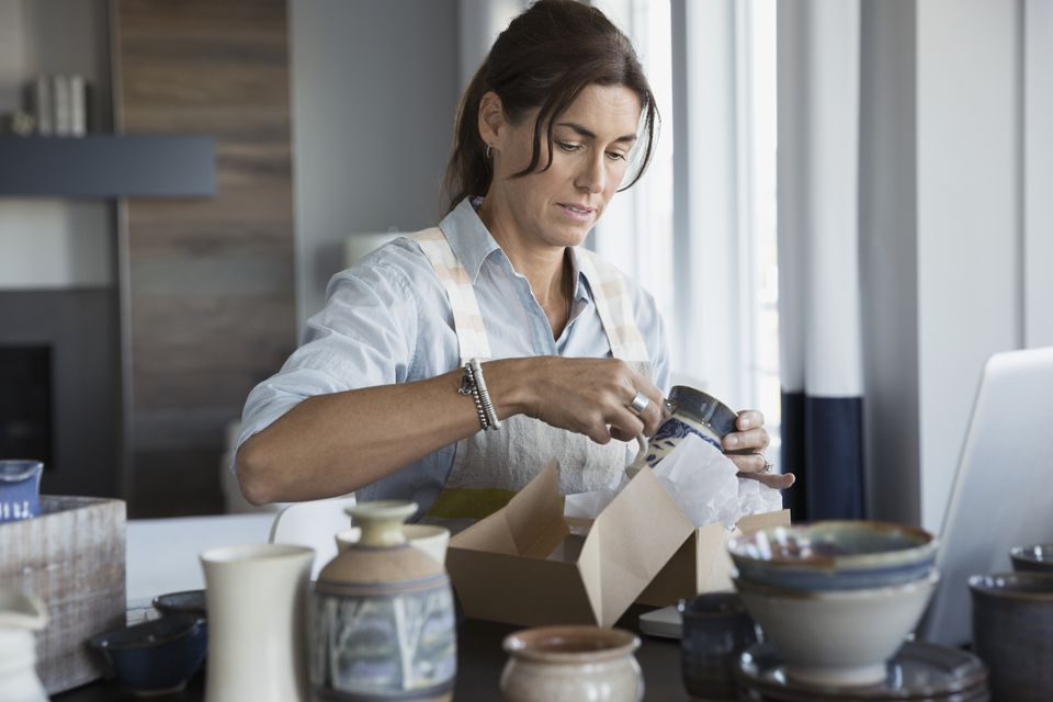 Woman packing pottery into boxes in a house