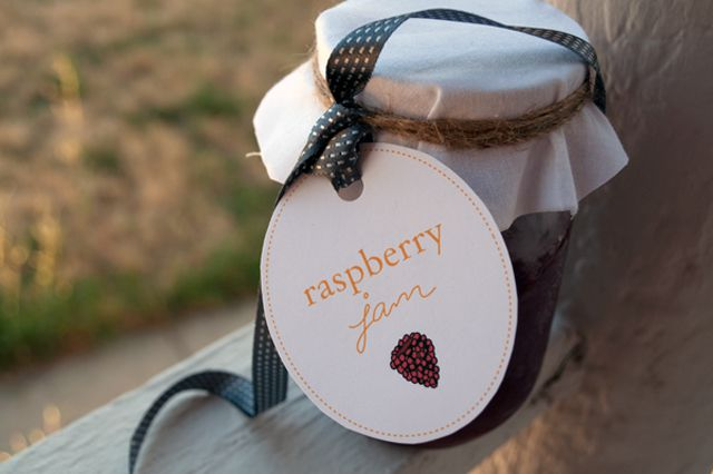 A canning jar with a raspberry jam label.