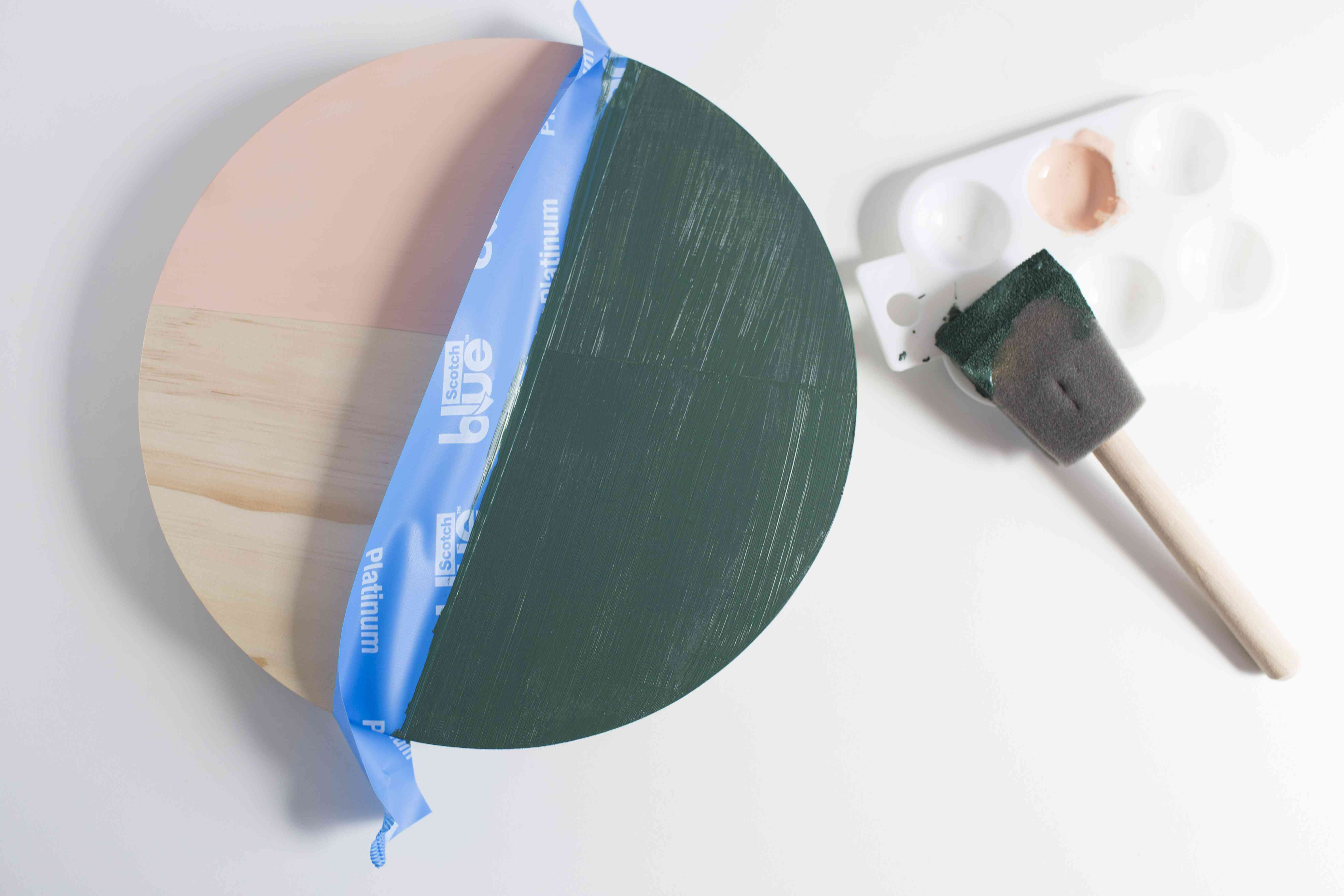 Wooden clock face with blue-green paint being painted on.