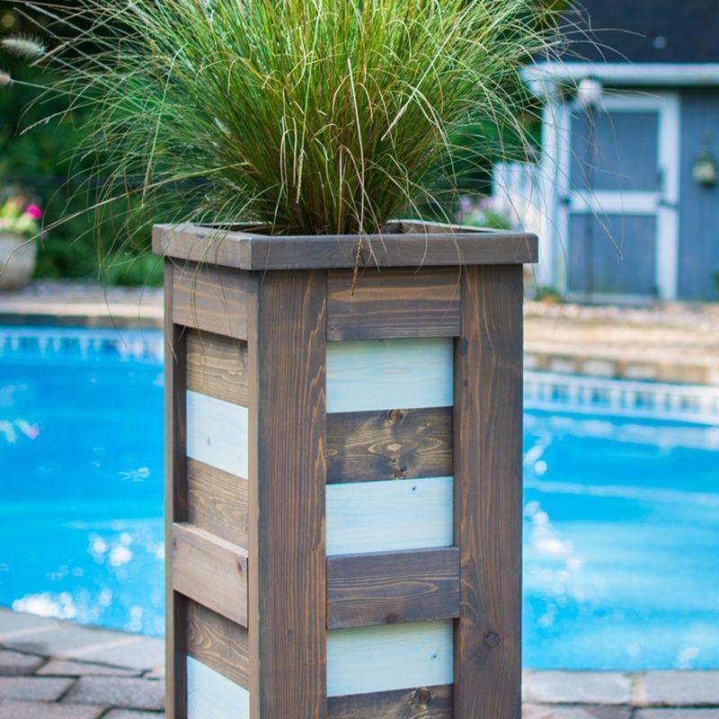 A tall cedar planter by a pool