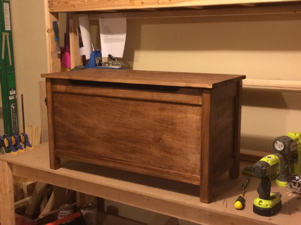 A wooden toy box with a lid