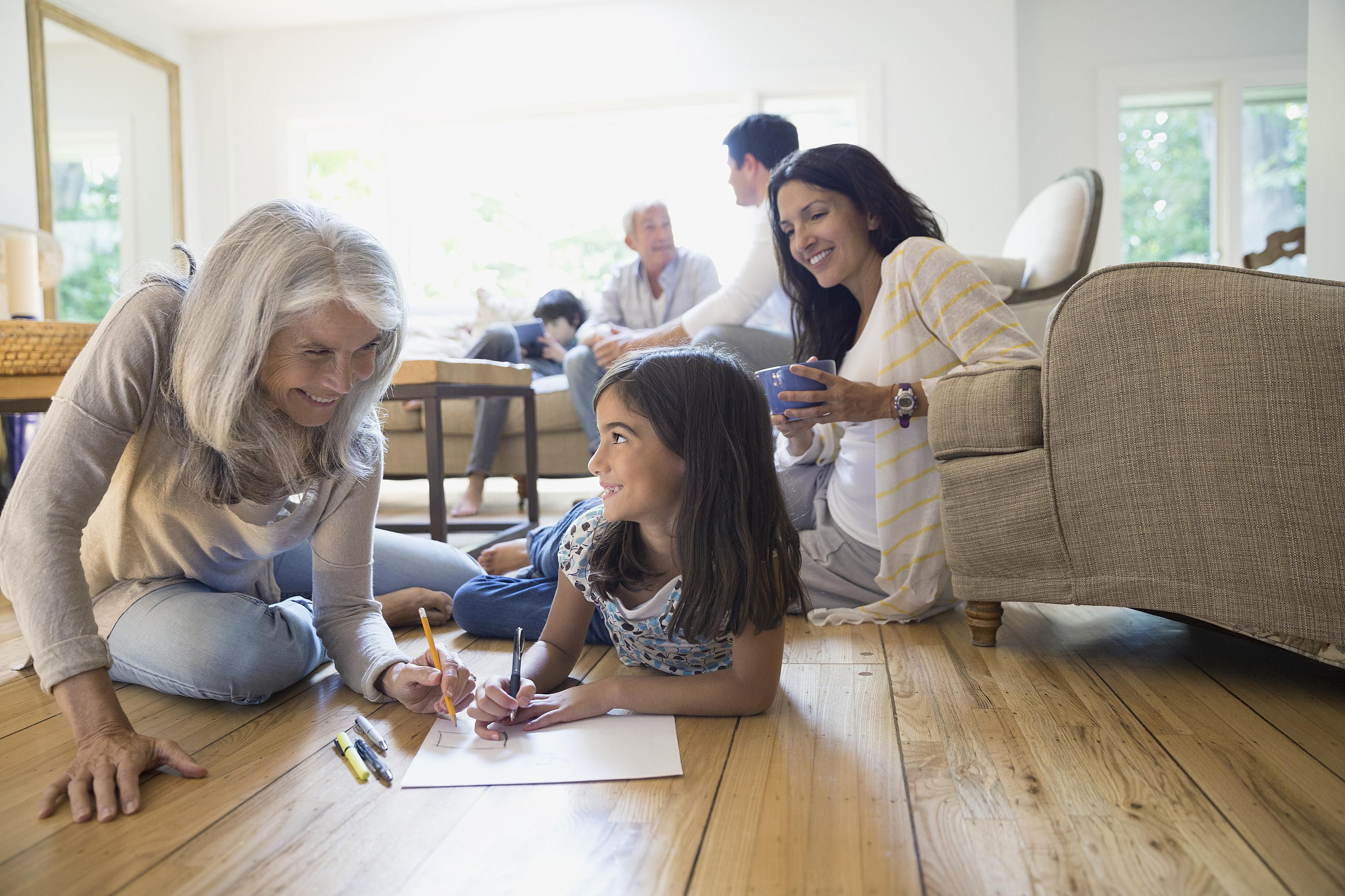 grandmother and granddaughter coloring in living room