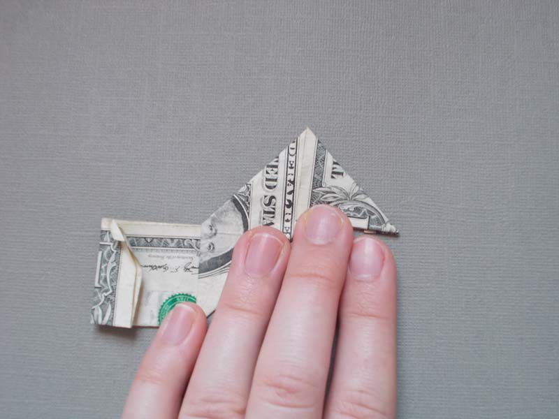 A dollar bill in stage four of an origami star