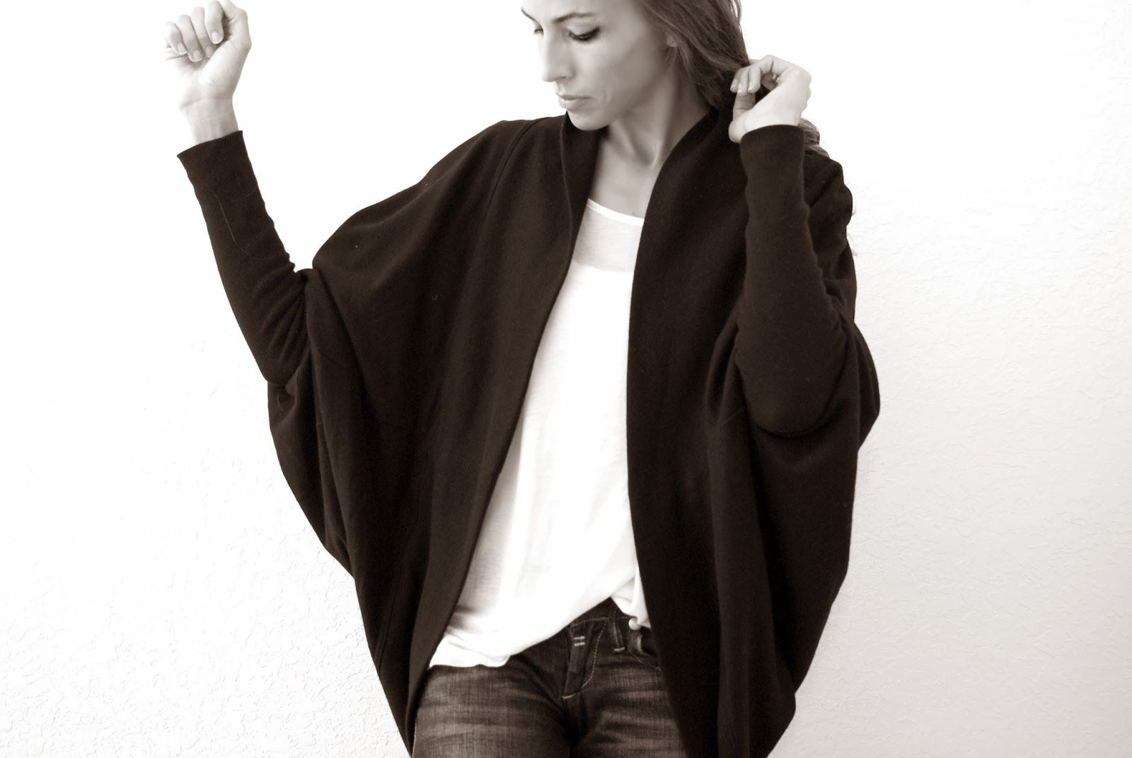 A woman wearing a black cardigan with a white tshirt
