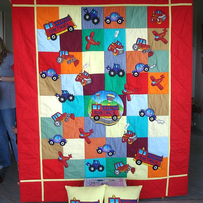 Red quilt with numerous transportation vehicles and two firetruck pillows.