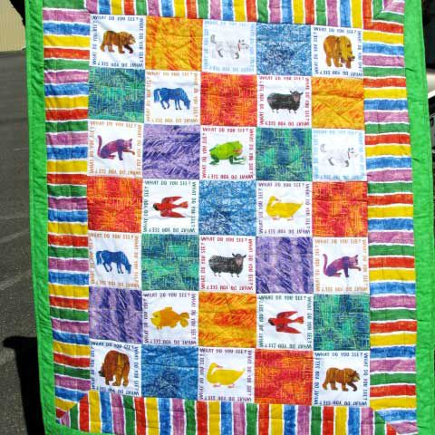 Person holding green quilt with characters from Brown Bear, Brown Bear book.