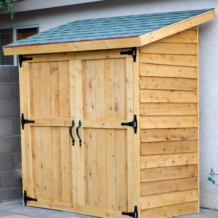 A storage shed made out of cedar fence planks