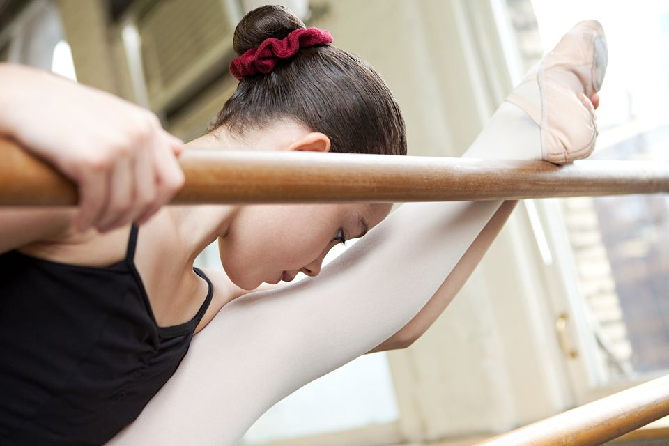 Ballerina stretching at barre