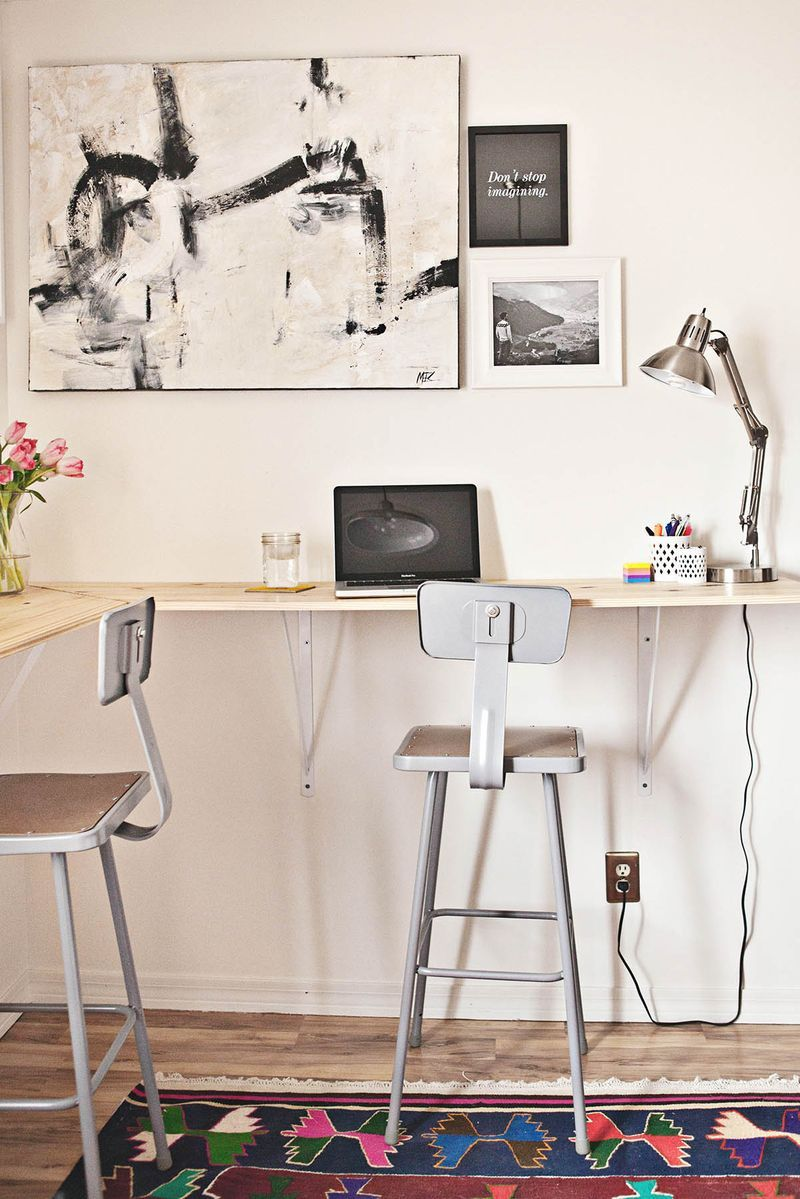 Wooden desk wrapped around a corner attached to a wall.
