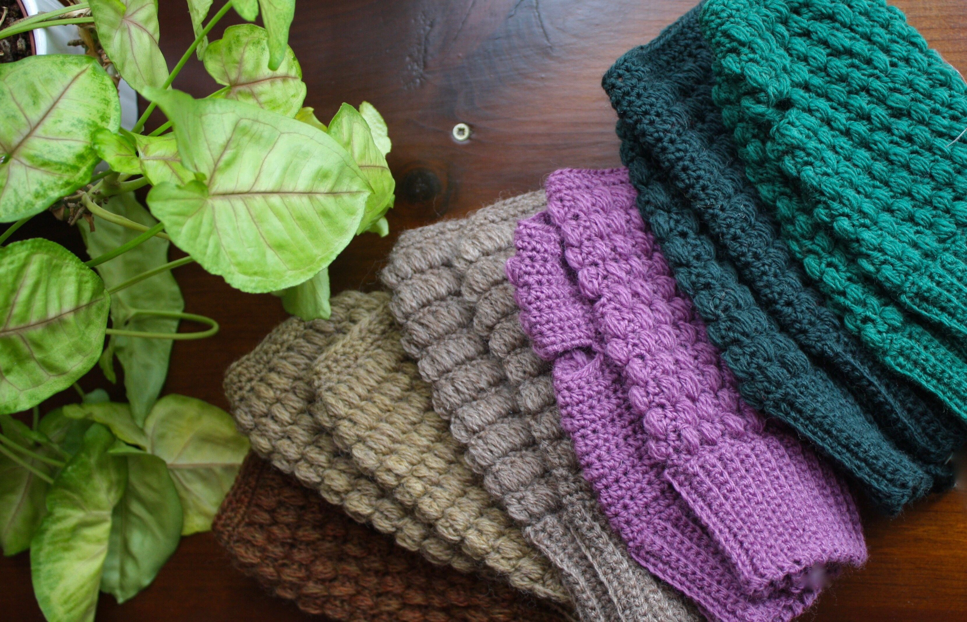 Close-Up Of Woolen Gloves By Plant On Table