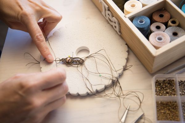 Lifestyle concept, work from home to reinvent your life: close-up of woman hands making macrame knotted jewelry with stone beads and tools on light wooden table