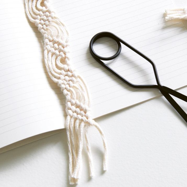 A macrame bookmark laying on a notebook