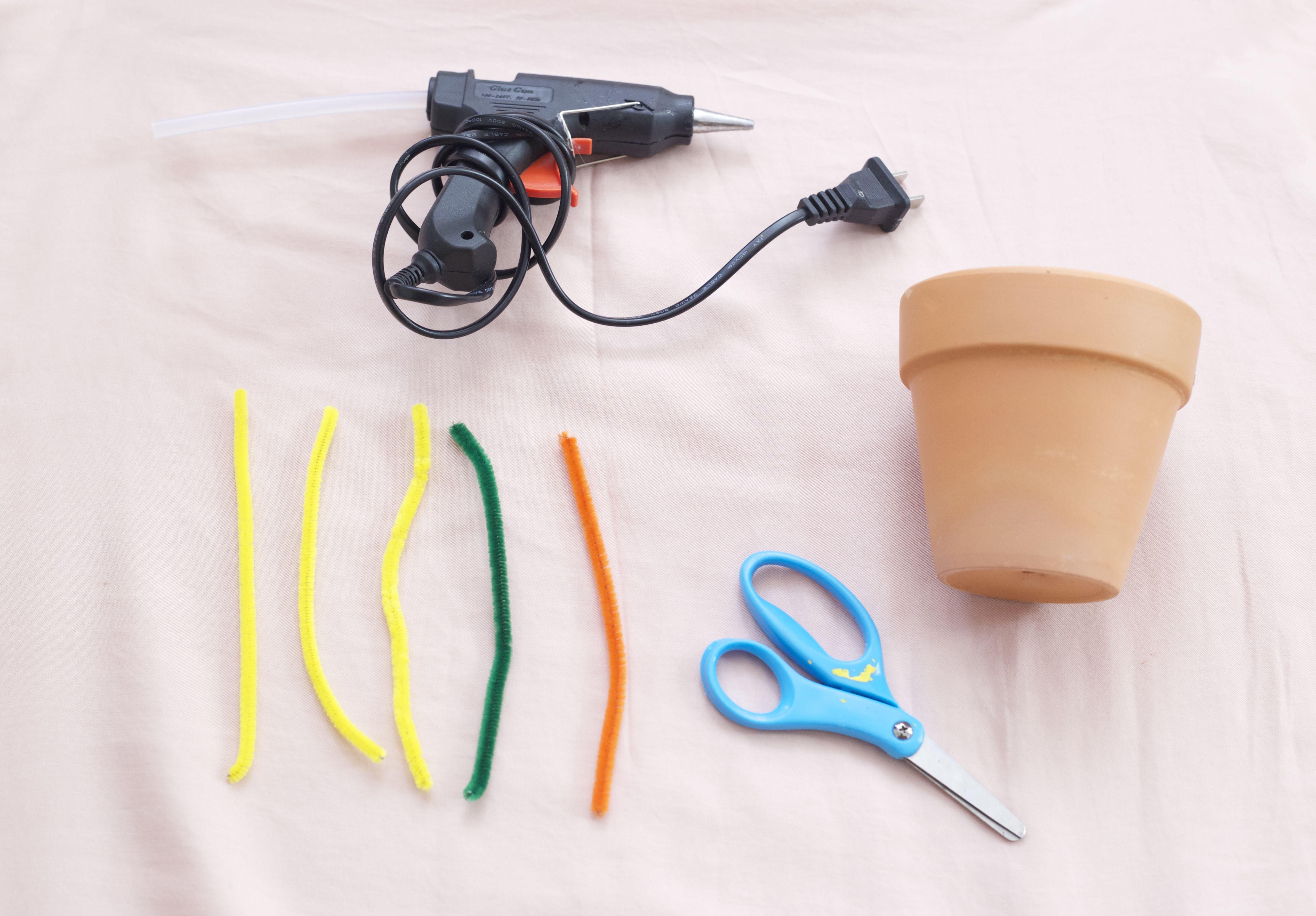 Hot glue gun, pipe cleaners, flower pot, and scissors