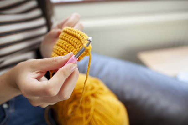 Young woman crocheting with yellow wool